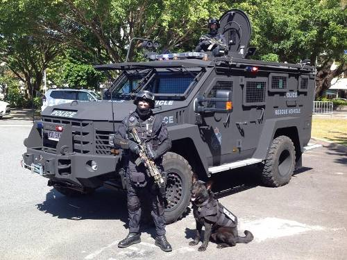 Cop and dog with military grade vehicle, weapons, and other equipment.