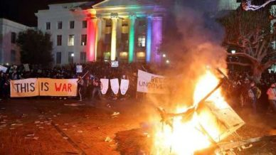 "Berkley students riot against Milo Yiannopoulos in front of rainbow colored building with signs: ""This is war"" and ""Become ungovernable."""