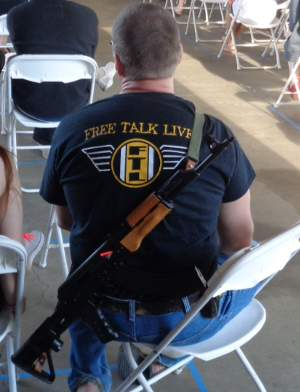 Man at PorcFest with a Free Talk Live shirt and an AK-47.