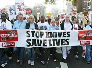"Protest marchers with a banner that says, ""Stop knives, save lives."""