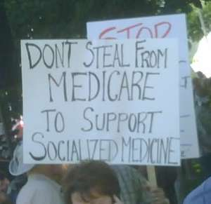"Protestor with sign: ""Don't steal from Medicare to support socialized medicine."""